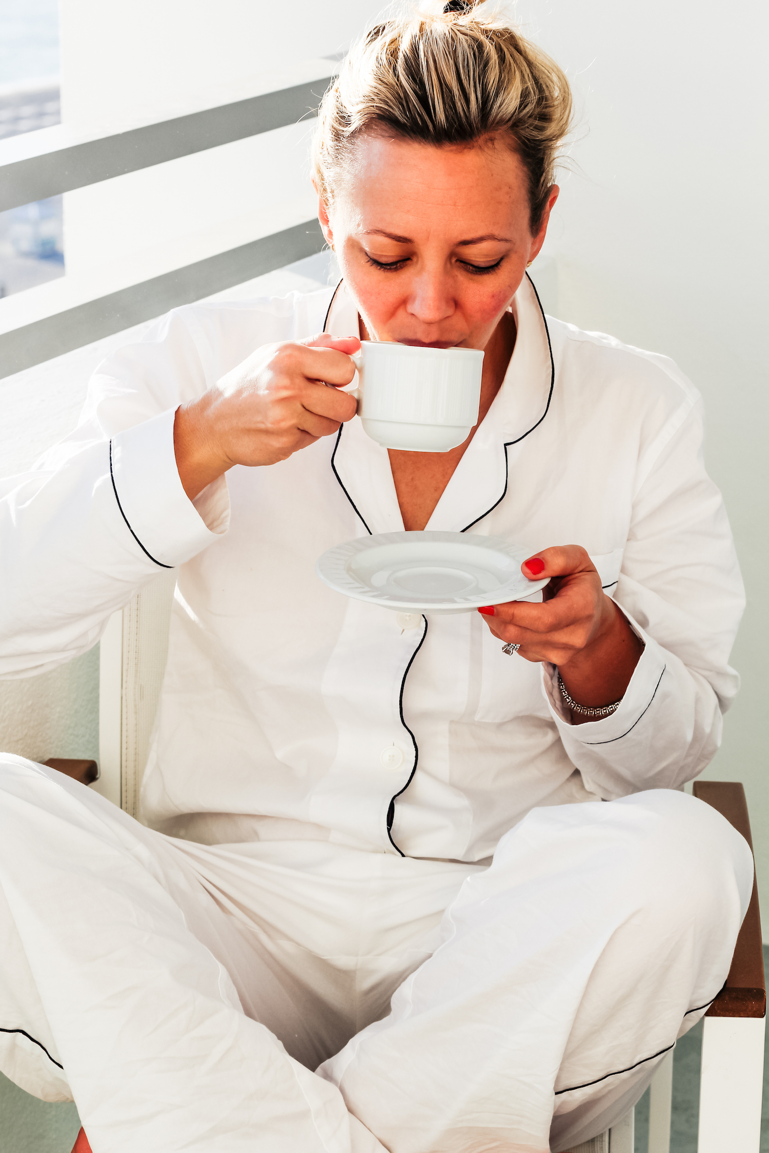 girl sipping coffee in everlane oxford pajamas